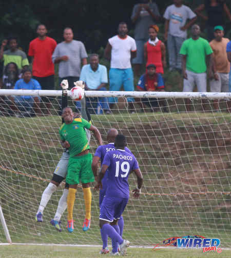 Photo: Defence Force goalkeeper Keron Graham (partially hidden) keeps out a header by Guaya United striker Carlon Hughes during 2015/16 CNG National Super League action yesterday in Guayaguare. (Courtesy Nicholas Bhajan/Wired868)
