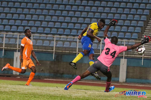Photo: Defence Force midfielder Sean Narcis (centre) heads past Club Sando goalkeeper Kelvin Henry (right) while Devon Modeste looks on during 2015/16 Pro League action. (Courtesy Chevaughn Christopher/Wired868)