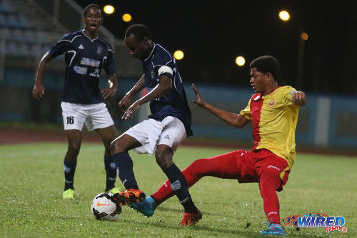 "Photo: Morvant Caledonia United captain Kareem ""Tiny"" Joseph (centre) keeps the ball from 15 year old North East Stars winger Keshon Hackshaw during 2015/16 Pro League action yesterday in Couva. Looking on is Morvant Caledonia defender Antonio Joseph. (Courtesy Chevaughn Christopher/Wired868)"