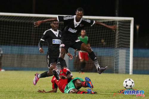 Photo: Central FC playmaker Ataulla Guerra (centre) leaps over San Juan Jabloteh captain Damian Williams during 2015/16 Pro League action yesterday at the Ato Boldon Stadium, Couva. (Courtesy Chevaughn Christopher/Wired868)