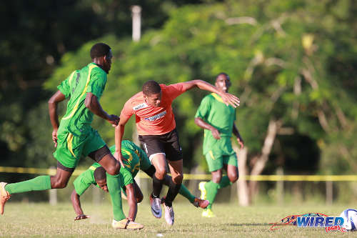 Photo: Real Maracas striker Christian Thomas (centre) runs at the Stokely Vale defence during 2015/16 CNG NSL Premiership action at the Maracas Recreation Ground. (Courtesy Nicholas Bhajan/Wired868)