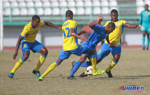 Photo: Police FC winger Christon Thomas (second from right) tries to elude Defence Force players Sean Narcis (right), Jemel Sebro (centre) and Rodell Elcock during 2015/16 Pro League action yesterday in Malabar. (Courtesy Nicholas Bhajan/Wired868)