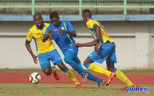 Photo: Police FC attacker Kareem Freitas (centre) tries to escape from Defence Force players Ross Russell Jr (right) and Akile Edwards during 2015/16 Pro League action yesterday in Malabar. (Courtesy Nicholas Bhajan/Wired868)