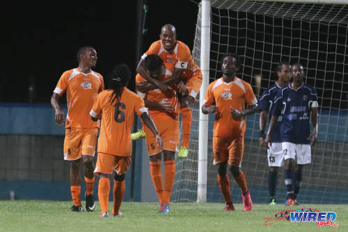 Photo: Club Sando captain Kern Cupid takes a lift from goal scorer Amritt Gildharry during 2015/16 Pro League action against Morvant Caledonia United, earlier this month, at the Ato Boldon Stadium, Couva. (Courtesy Chevaughn Christopher/Wired868)