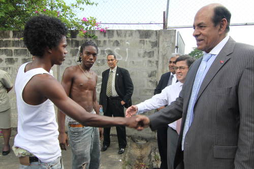 Photo: Former Education Minister Tim Gopeesingh (right) greets a young resident in Success Laventille. (Copyright news.gov.tt)