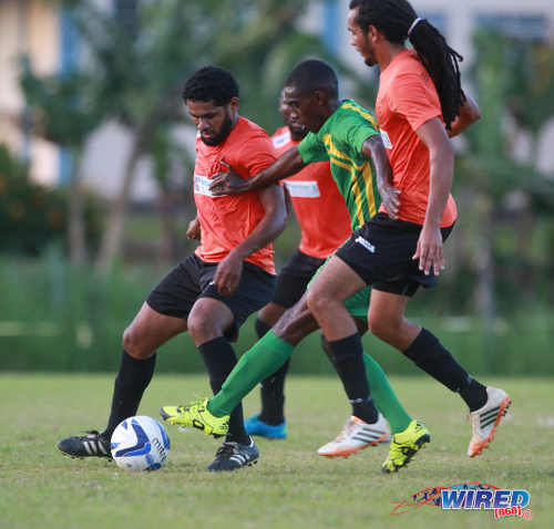 Photo: Real Maracas captain Kerwyn Bartholomew (left) and teammate Dillon Bartholomew (right) try to keep a leash on Stokely Vale winger Kerwin Thomas during 2015/16 CNG NSL Premiership action yesterday at the Maracas Recreation Ground. (Courtesy Nicholas Bhajan/Wired868)