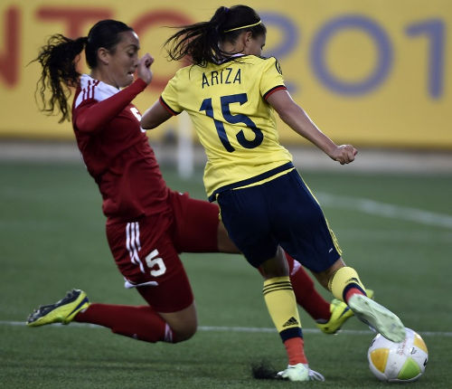 Photo: Trinidad and Tobago captain and 2014 TTFA Player of the Year Arin King (left) dives in to tackle Colombia's Tatiana Ariza during the Toronto 2015 Pan American Games. (Copyright AFP 2016)