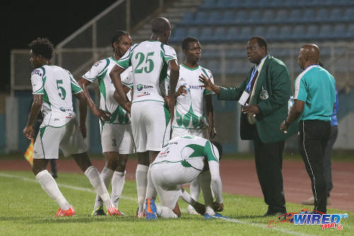 Photo: W Connection coach Stuart Charles-Fevrier (second from right) and assistant coach Earl Jean (far right) speak to their players during a break between the action against Atlantico FC in 2016 Caribbean Club Championship action. (Courtesy Chevaughn Christopher/Wired868)