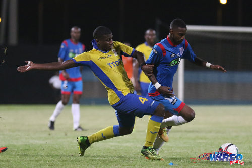 Photo: St Ann's Rangers captain Johan Peltier (right) tries to escape from Defence Force midfielder Dave Long during TT Pro League action at the Ato Boldon Stadium on 1 March 2016. (Courtesy Chevaughn Christopher/Wired868)