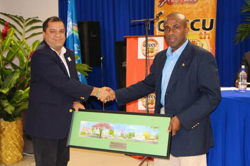 Photo: COPOS Credit Union manager and Trinidad and Tobago Gymnastics Federation (TTGF) president David Marquez (left) makes a presentation to GECCU president Clarence Harry. (Copyright GECCU)