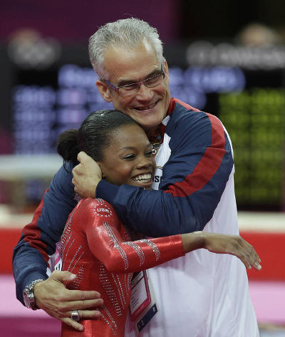 Photo: United States head coach John Geddert (right) hugs gymnast Gabrielle Douglas at the London 2012 Olympic Games. Geddert trains Trinidad and Tobago gymnast, Thema Williams, at his gym in Michigan. (Courtesy Desert News)