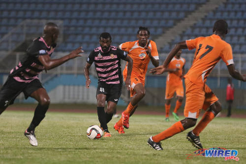 Photo: Veteran poacher Kerry Baptiste (centre) leads the charge for North East Stars during TT Pro League action at the Ato Boldon Stadium on 1 March 2016. Baptiste's teammate (far left) Anthony Wolfe tries to anticipate his pass while Club Sando midfield anchor Shannon Phillip (second from right) tries to keep up. (Courtesy Chevaughn Christopher/Wired868)