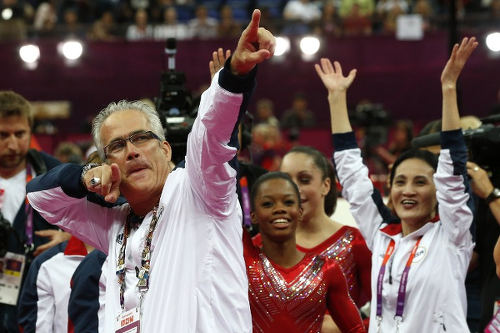 Photo: US women gymnastics team's coach John Geddert celebrates with the rest of the team after the US won gold in the artistic gymnastics event of the London Olympic Games on 31 July 2012. Geddert coaches Trinidad and Tobago gymnast Thema Williams in Michigan. (Copyright AFP 2016/Thomas Coex)
