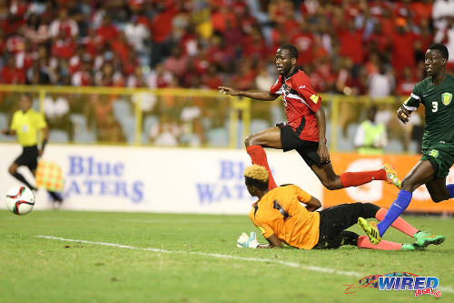 Photo: Trinidad and Tobago playmaker Kevin Molino (top) buries the ball past St Vincent and the Grenadines goalkeeper Lemus Christopher during Russia 2018 World Cup qualifying action at the Hasely Crawford Stadium, Port of Spain on 29 March 2016. Trinidad and Tobago won 6-0. (Courtesy: Allan V Crane/CA-images/Wired868)