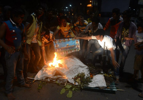 Photo: Indian cricket fans burn portraits of players as they stage a funeral of the Indian cricket team in the streets of Siliguri on 31 March 2016, after India's defeat in the men's semi-final match against the West Indies. (Copyright AFP 2016/Diptendu Dutta)