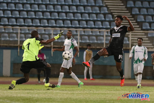 Photo: Central FC forward Nicholas Dillon (right) is closed down by DIRECTV W Connection goalkeeper Terrence Lewis during the Lucozade Sport Goal Shield semifinals on 15 April 2016. Connection won 4-2. (Courtesy Chevaughn Christopher/Wired868)