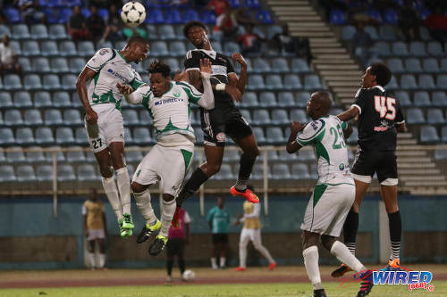 Photo: Central FC forward Nicholas Dillon (centre) challenges W Connection defenders Jelani Peters (far left) and Maurice Ford (second from left) in the air during the Lucozade Sport Goal Shield semifinals on 15 April 2016. Connection won 4-2. (Courtesy Chevaughn Christopher/Wired868)
