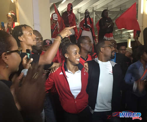 Photo: Trinidad and Tobago gymnast Thema Williams (centre) hugs relatives as she is welcomed home from Rio by her fans at the Piarco International Airport on Wednesday 20 April 2016. (Courtesy Lou-Ann Sankar/Wired868)
