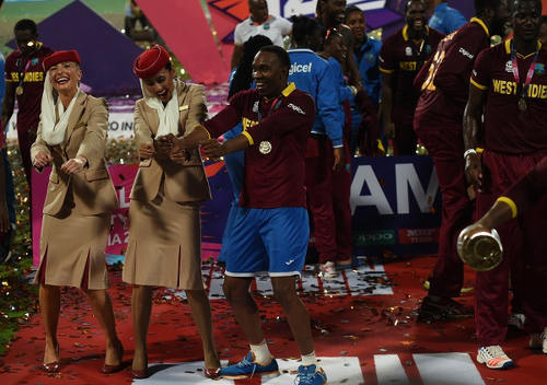 Photo: West Indies cricket star Dwayne Bravo (centre) dances with air hostesses after victory in the World T20 cricket tournament final match against England at The Eden Gardens Cricket Stadium in Kolkata on 3 April 2016. (Copyright AFP 2016/Indranil Mukherjee)