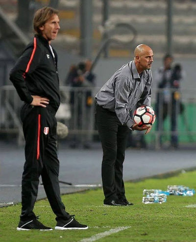 Photo: Trinidad and Tobago National Senior Team coach Stephen Hart (right) gives the ball back while Peru coach Ricardo Gareca looks on during international friendly action in Lima on 23 May 2016. Peru won 4-0.