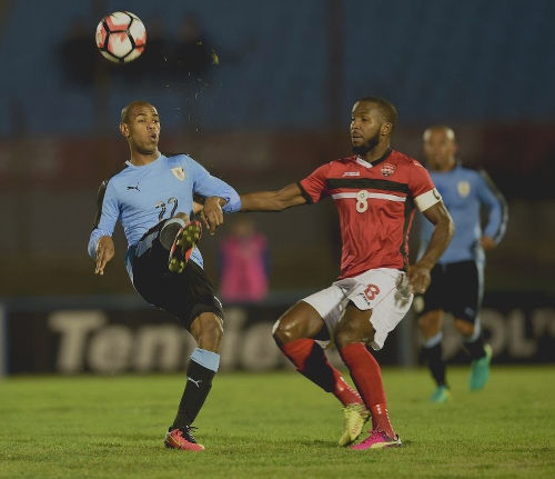 Photo: Uruguay attacker Diego Rolan (left) tries to keep the ball from Trinidad and Tobago midfielder Khaleem Hyland during friendly international action at the Centenario Stadium in Montevideo on 27 March 2016. (Copyright Miguel Rojo/AFP 2016)