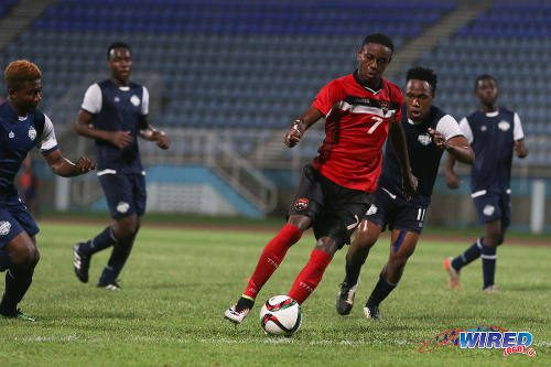 Photo: Trinidad and Tobago National Under-20 winger Isaiah Hudson (centre) runs at the Turks and Caicos defence during Caribbean Cup qualifying action at the Ato Boldon Stadium on 17 June 2016. T&T won 11-0. (Courtesy Chevaughn Christopher/Wired868)