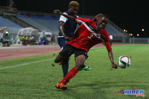 Photo: Trinidad and Tobago National Under-20 right back Kori Cupid (right) tries to keep his balance after pressure from a Turks and Caicos player during Caribbean Cup qualifying action at the Ato Boldon Stadium on 17 June 2016. T&T won 11-0. (Courtesy Chevaughn Christopher/Wired868)