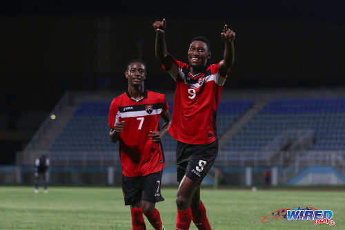 Photo: Trinidad and Tobago striker Nicholas Dillon (right) celebrates one of his five goals against Turks and Caicos alongside teammate Isaiah Hudson during Caribbean Cup qualifying action at the Ato Boldon Stadium on 17 June 2016. T&T won 11-0. (Courtesy Chevaughn Christopher/Wired868)