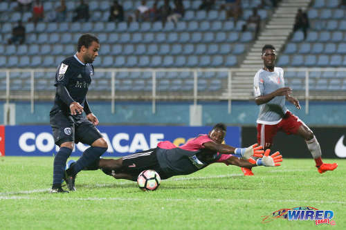 Photo: Central FC custodian Javon Sample (centre) dives in vain to try to deny Sporting Kansas City attacker Kevin Ellis (left) while defender Elton John looks on during 2016 CONCACAF Champions League action at the Ato Boldon Stadium in Couva on 16 August 2016. Both teams played to a 2-2 draw. (Courtesy Chevaughn Christopher/Wired868)