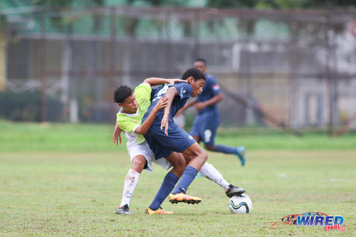 Photo: QRC midfielder Kalev Keil (right) is tackled by a St Augustine player during SSFL Premier Division action at the QRC grounds on 8 September 2016. (Courtesy Chevaughn Christopher/Wired868)