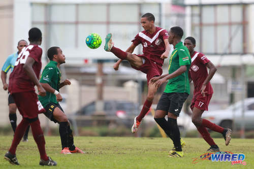 Photo East Mucurapo midfielder Joshua Constantine (centre) shows his studs as he goes for the ball while St Benedict's College midfielder Kristoff Burkett (second from left) has second thoughts during SSFL Premier Division action at Mucurapo Road on 6 October 2016. (Courtesy Nicholas Bhajan/Wired868)