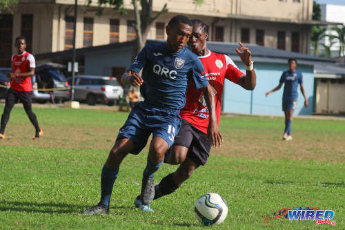 Photo: Queen's Royal College playmaker John-Paul Rochford (left) tries to keep the ball from St Anthony's College winger Haile Beckles during SSFL action at QRC grounds on 26 October 2016. (Courtesy Nicholas Williams/Wired868)