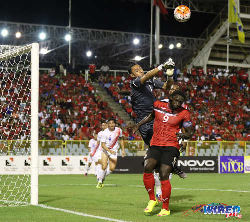 Photo: Costa Rica goalkeeper Keylor Navas (top) punches the ball away from Trinidad and Tobago forward Kenwyne Jones during Russia 2018 World Cup qualifying action at the Hasely Crawford Stadium on 11 November 2016. (Courtesy Sean Morrison/Wired868)