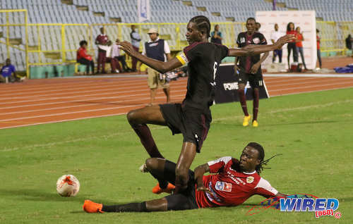 Photo: St Anthony's College defender Ronaldo Jacob (right) tackles East Mucurapo Secondary captain Aquinde Marslin during the North Zone Intercol semifinal at the Hasely Crawford Stadium on 16 November 2016. (Copyright Sean Morrison/Wired868)