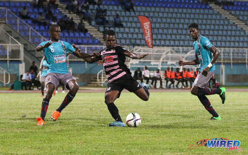 Photo: Ma Pau Stars striker Jerrel Britto (centre) lines up a shot while Morvant Caledonia United defenders Taje Commissiong (left) and Ordell Flemming look on during Pro League at the Ato Boldon Stadium in Couva on 22 November 2016. (Courtesy Sean Morrison/Wired868)