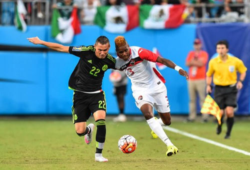 Photo: Trinidad and Tobago winger Joevin Jones (right) battles with Mexico midfielder Paul Aguilar during a 2015 CONCACAF Gold Cup Group C match in Charlotte, North Carolina, on 15 July 2015. (Copyright AFP 2016/Nicholas Kamm)