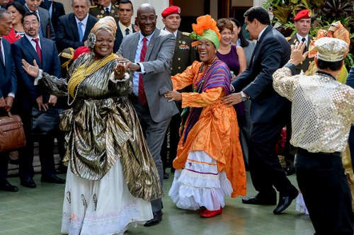 Photo: Trinidad and Tobago Prime Minister Keith Look Loy (second from left) and Venezuela President Nicolas Maduro (right) dance to calypso after a meeting at Miraflores presidential palace in Caracas on 5 December 2016. (Copyright AFP 2017/Federico Parra)