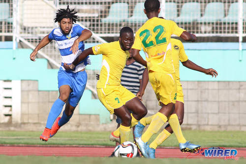 Photo: Presentation College (San Fernando) winger Nion Lammy (left) tries to escape from Signal Hill Secondary defender Nkosei Chance (centre) during the National Intercol Semifinals at the Mannie Ramjohn Stadium on 3 December 2016. (Courtesy Chevaughn Christopher/Wired868)