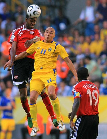 Photo: Trinidad and Tobago defender Dennis Lawrence (left) wins a header from Sweden forward Henrik Larsson during the Germany 2006 World Cup at the Dortmund Stadium. (Copyright AFP 2017)
