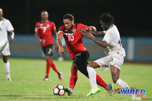 Photo: Trinidad and Tobago forward Shahdon Winchester (left) holds off a Suriname defender during 2017 Gold Cup playoff action against Suriname at the Ato Boldon Stadium, Couva on 4 January 2017. (Courtesy Chevaughn Christopher/Wired868)