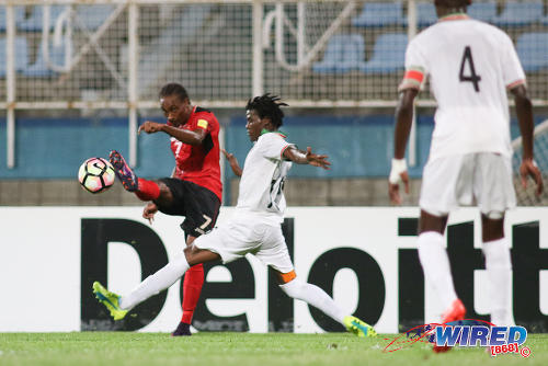 Photo: Trinidad and Tobago winger Tyrone Charles (left) whips a cross past Suriname right back Miquel Darson during 2017 Gold Cup playoff action at the Ato Boldon Stadium, Couva on 4 January 2017. (Courtesy Chevaughn Christopher/Wired868)