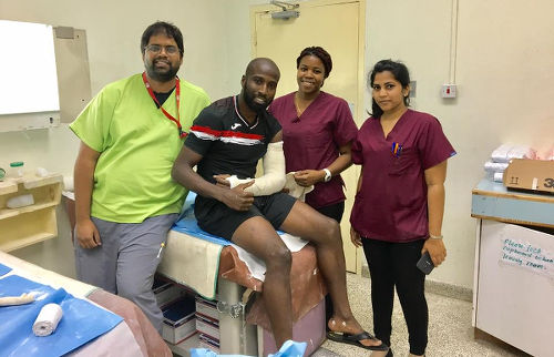 Photo: Trinidad and Tobago forward Cornell Glen (centre) poses with staff at the San Fernando General Hospital after breaking his arm in a Gold Cup qualifier against Haiti on 8 January 2017.