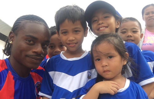 Photo: Trinidad and Tobago midfielder Darren Mitchell (left) meets young football fans of Davao Aguilas FC in the Philippines.