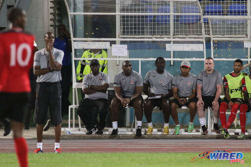 Photo: Trinidad and Tobago National Senior Team head coach Dennis Lawrence (second from left) and half of his technical staff who are (from right) Stephen Bradley, Riedoh Berdien, Ross Russell, Sol Campbell and Stuart Charles-Fevrier take in the action during their friendly international outing against Barbados on 10 March 2017. Lawrence was without assistant coach Stern John, who lost his daughter, Nikela, to a tragic mishap on the eve of the game. (Courtesy Chevaughn Christopher/Wired868)
