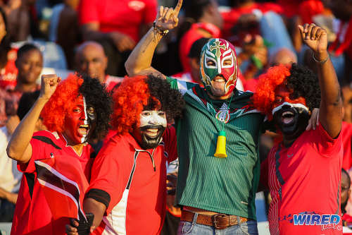 Photo: A Mexico football fan (centre) poses with Trinidad and Tobago football fans before kick off of the Russia 2018 World Cup qualifying meeting at the Hasely Crawford Stadium in Port of Spain on 28 March 2017. Mexico won 1-0. (Courtesy Chevaughn Christopher/Wired868)
