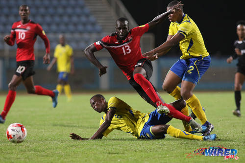 Photo: Trinidad and Tobago striker Jamille Boatswain (centre) tries to burst past two Barbados opponents during international friendly action at the Ato Boldon Stadium in Couva on 10 March 2017. Boatswain scored both goals in a 2-0 win for T&T. (Courtesy Chevaughn Christopher/Wired868)