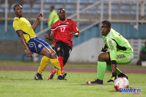 Photo: Trinidad and Tobago National Senior Team winger Jomoul Francois (centre) strokes the ball past Barbados goalkeeper Kishmar Primus (right) during international friendly action against Barbados at the Ato Boldon Stadium in Couva on 10 March 2017. (Courtesy Chevaughn Christopher/Wired868)