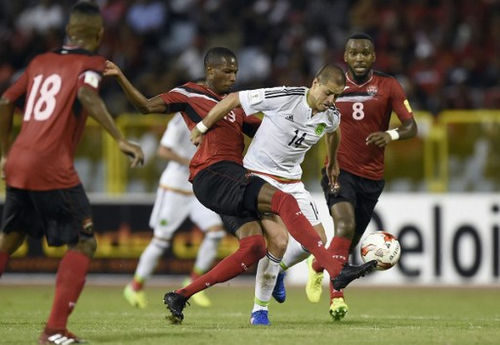Photo: Mexico forward Javier Hernandez (right) tries unsuccessfully to evade a tackle from Trinidad and Tobago midfielder Kevan George during 2018 FIFA World Cup qualifying action at the Hasely Crawford Stadium in Port of Spain on 28 March 2017. (Copyright AFP 2017/Alfredo Estrella)