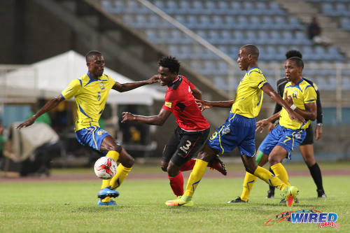 Photo: Trinidad and Tobago defender Triston Hodge (centre) tries to wriggle past some Barbados opponents during international friendly action at the Ato Boldon Stadium in Couva on 10 March 2017. (Courtesy Chevaughn Christopher/Wired868)
