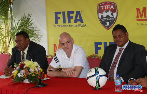 Photo: FIFA president Gianni Infantino (centre) momentarily loses his smile as he considers a Wired868 question on racism at a press conference at the Ato Boldon Stadium in Couva on 10 April 2017. Sitting on either side of Infantino are TTFA president David John-Williams (left) and Sport Minister Darryl Smith. (Courtesy Sean Morrison/Wired868)